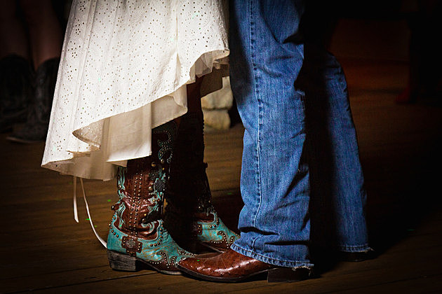 The bride and groom dancing in boots at a country wedding.